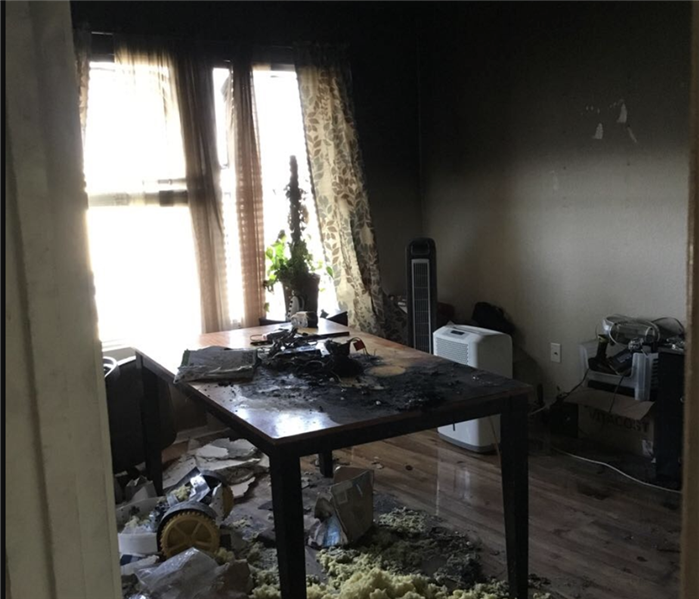 Dining room with table, walls and curtains have suffered major smoke damage and there is insulation on the floor